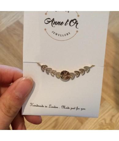 Bracelet personnalisé en plaqué or avec feuilles de laurier, gravé à la main par Annelor London à Wimbledon packaging